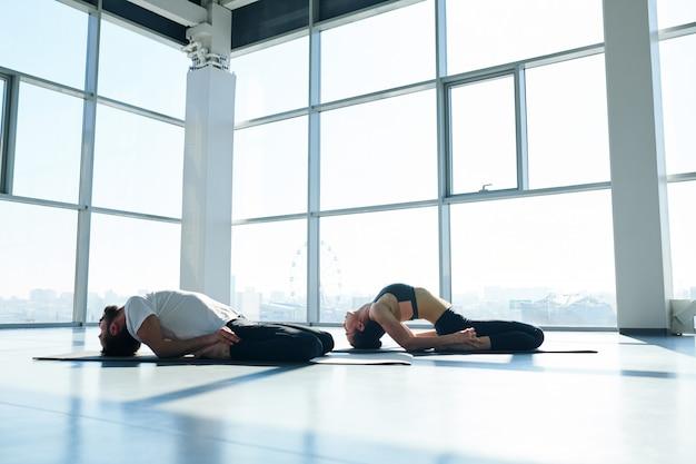 Junger sportlicher mann und frau in der aktivkleidung, die ihren rücken biegt, während boden während der yoga-praxis boden mit köpfen berührt