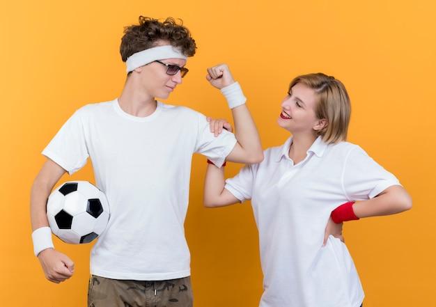Junger sportlicher paarmann, der bizeps zeigt fußballnex zu seiner lächelnden freundin über orange zeigt