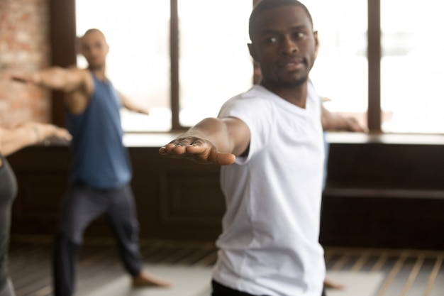 Junger sportlicher schwarzer mann in der übung des kriegers zwei