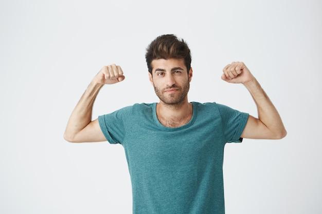 Junger sportlicher spanischer kerl im blauen t-shirt und in der stilvollen frisur, die das spielen mit muskeln zeigt, die für fotoshooting des sportmagazins posieren.