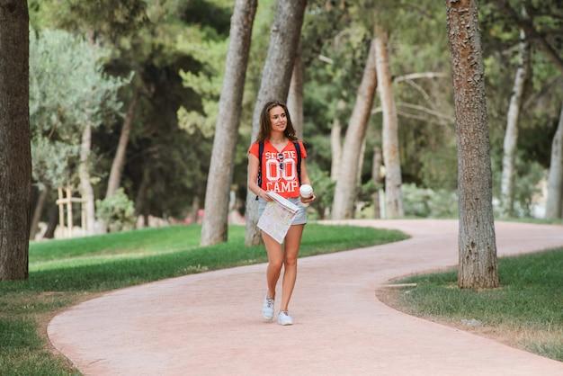 Junger sportlicher weiblicher reisender mit nettem lächeln eine karte im park studierend