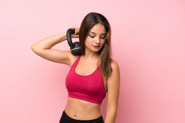 Junger sportmädchenhintergrund, der das gewichtheben mit kettlebell macht