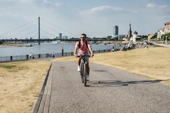 Junger Sportmann auf einem Fahrrad in einer europäischen Stadt. Sport in urbanen Umgebungen.