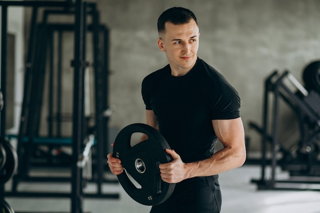 Junger sportmann, der an der turnhalle trainiert