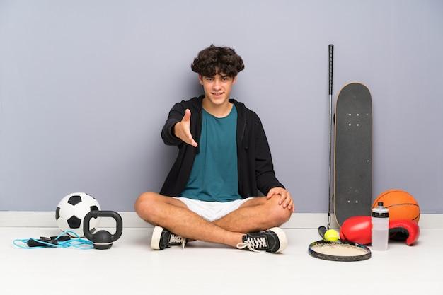 Junger sportmann, der auf dem boden um das händeschütteln vieler sportelemente nach viel sitzt