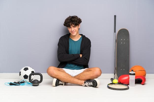 Junger sportmann, der auf dem boden um das lachen vieler sportelemente sitzt