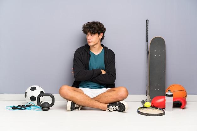 Junger sportmann, der auf dem boden um viele sportelemente denkt eine idee sitzt