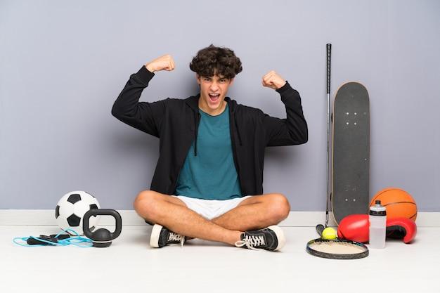 Junger sportmann, der auf dem boden um viele sportelemente feiert einen sieg sitzt