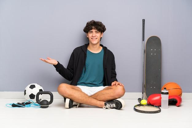 Junger sportmann, der auf dem boden um viele sportelemente halten copyspace eingebildet auf der palme sitzt