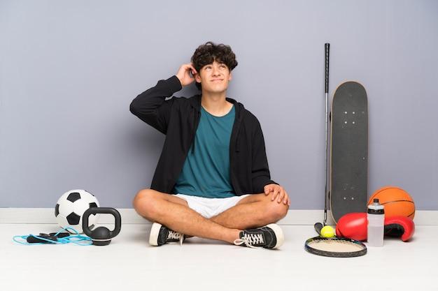 Junger sportmann, der auf dem boden um viele sportelemente hat zweifel und mit verwirren gesichtsausdruck sitzt