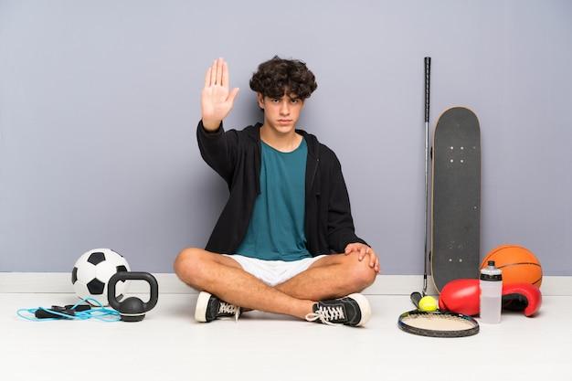 Junger sportmann, der auf dem boden um viele sportelemente machen halt sitzt, gestikulieren mit ihrer hand