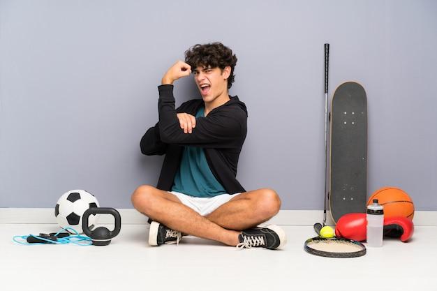 Junger sportmann, der auf dem boden um viele sportelemente machen starke geste sitzt