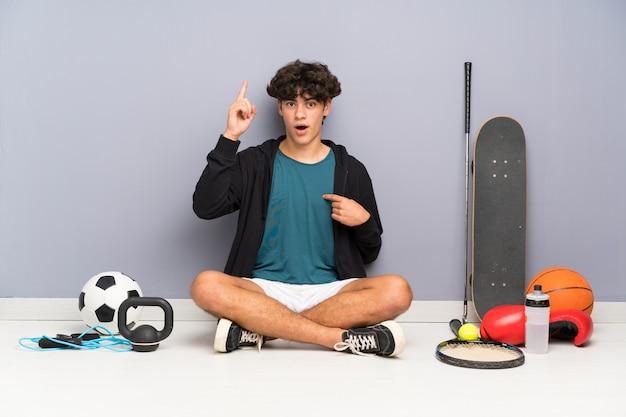 Junger sportmann, der auf dem boden um viele sportelemente mit überraschungsgesichtsausdruck sitzt