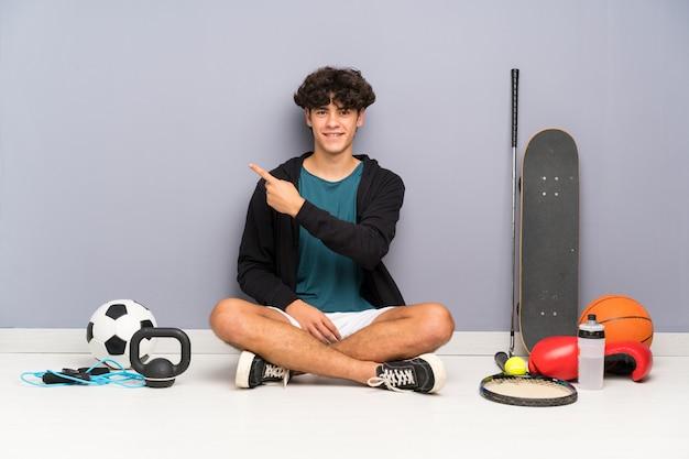 Junger sportmann, der auf dem boden um viele sportelemente zeigen finger auf die seite sitzt