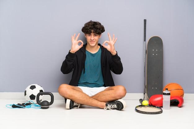 Junger sportmann, der auf dem boden um viele sportelemente zeigt ein okayzeichen mit den fingern sitzt