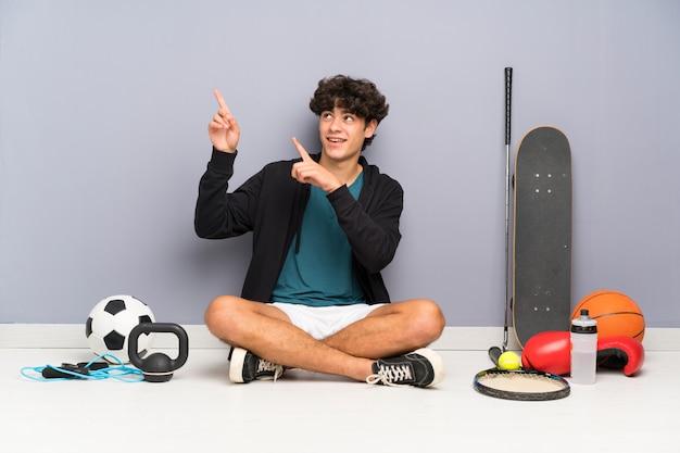 Junger sportmann, der auf dem boden um viele sportelemente zeigt mit dem zeigefinger eine großartige idee sitzt