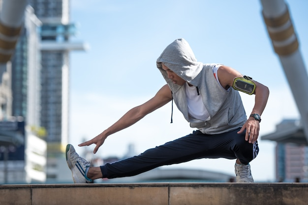 Junger sportmann, der beine auf der modernen stadt ausdehnt.