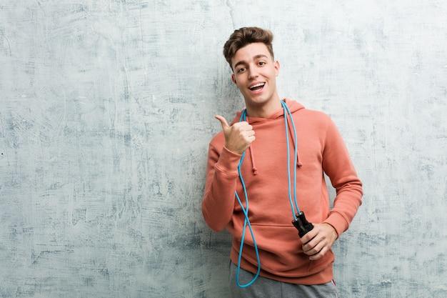 Junger sportmann, der ein seilspringen lächelt hält, freundlich zeigend mit dem zeigefinger weg