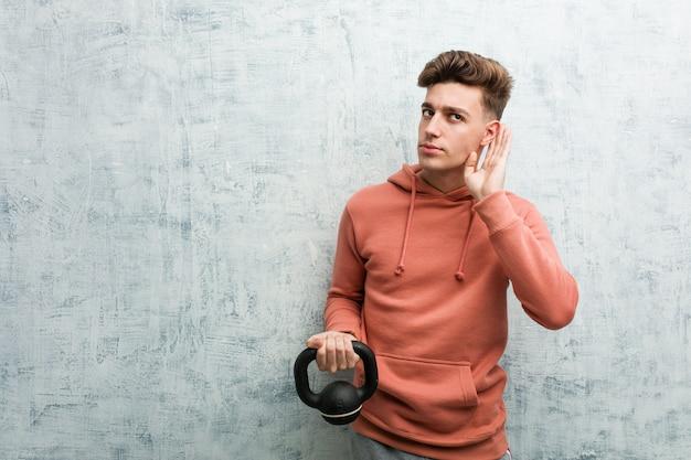 Junger sportmann, der einen dummkopf versucht, einen klatsch zu hören hält.