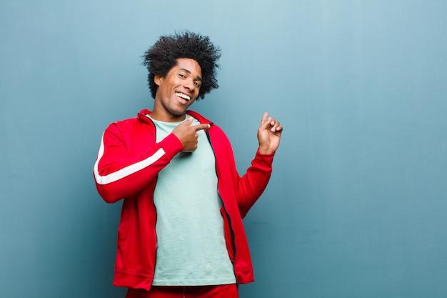 Junger sportmann, der fröhlich lächelt und beiläufig zeigt, um platz auf der seite zu kopieren, sich glücklich und zufrieden über grunge wand fühlend