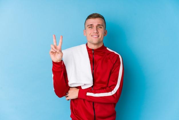 Junger sportmann, der nummer zwei mit den fingern zeigt.