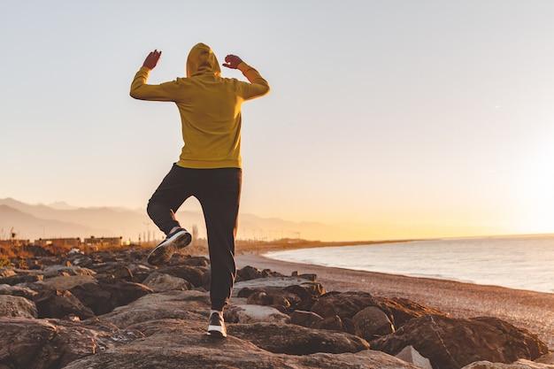 Junger sportmann in der haube, die einen sprung auf den felsen auf see- und gebirgshintergrund bei sonnenuntergang macht