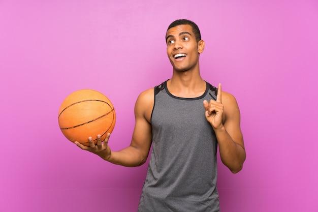Junger sportmann mit ball des basketballs über der lokalisierten purpurroten wand, die beabsichtigt, die lösung beim anheben eines fingers zu verwirklichen
