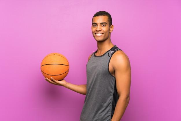 Junger sportmann mit ball des basketballs über lokalisierter purpurroter wand viel lächelnd