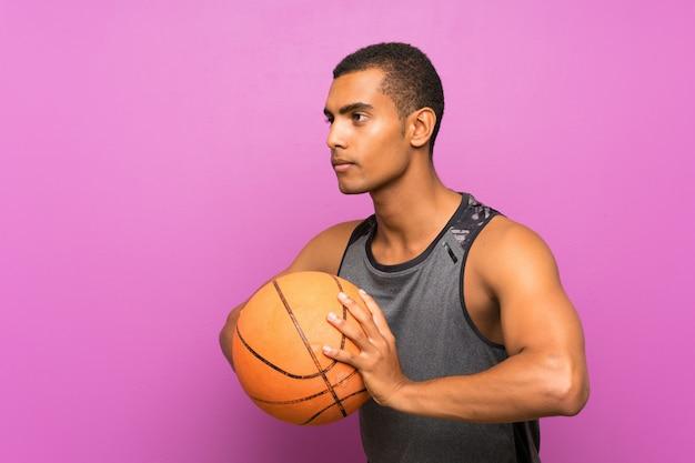 Junger sportmann mit ball des basketballs über lokalisierter purpurroter wand