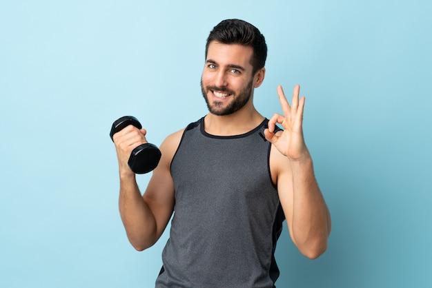 Junger sportmann mit bart, der gewichtheben macht, das ok zeichen mit den fingern zeigt