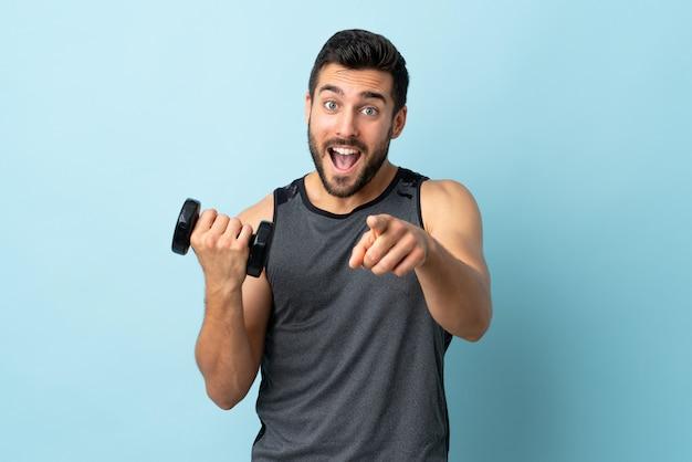 Junger sportmann mit bart, der gewichtheben zeigt finger auf sie mit einem selbstbewussten ausdruck