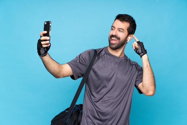 Junger sportmann mit bart über dem lokalisierten blau, das ein selfie macht