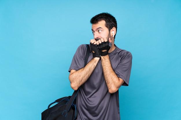 Junger sportmann mit bart über lokalisiertem blauem hintergrund nervös und erschrocken, hände zum mund setzend