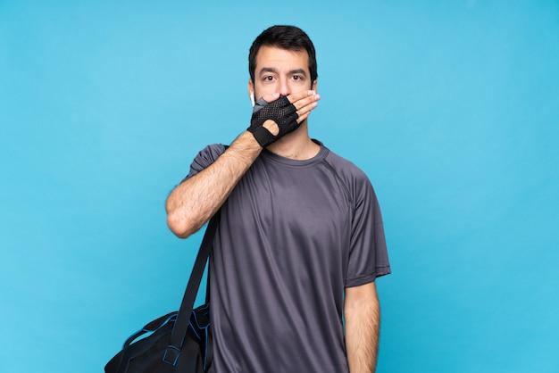 Junger sportmann mit bart über lokalisiertem blauem wandverkleidungsmund mit den händen