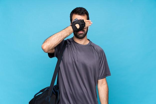 Junger sportmann mit bart über lokalisierten blauen bedeckungsaugen durch hände. ich will nichts sehen