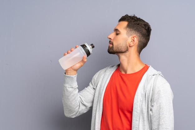 Junger sportmann mit einer flasche wasser