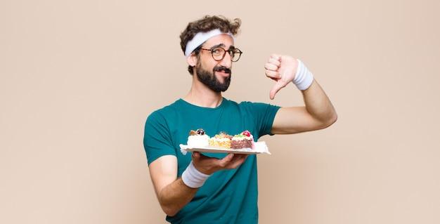 Junger sportmann mit kuchen an der wand
