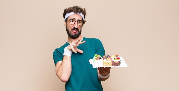 Junger sportmann mit kuchen gegen flache wand
