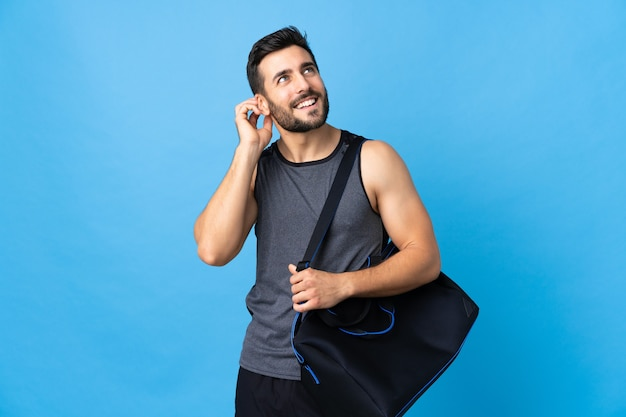 Junger sportmann mit sporttasche lokalisiert auf blauem hintergrund, der eine idee denkt