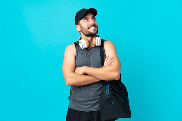 Junger sportmann mit sporttasche lokalisiert auf blauer wand, die beim lächeln nach oben schaut