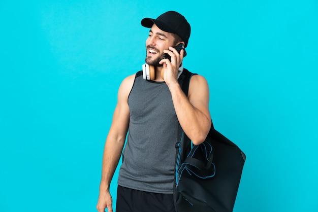 Junger sportmann mit sporttasche lokalisiert auf blauer wand, die ein gespräch mit dem mobiltelefon hält
