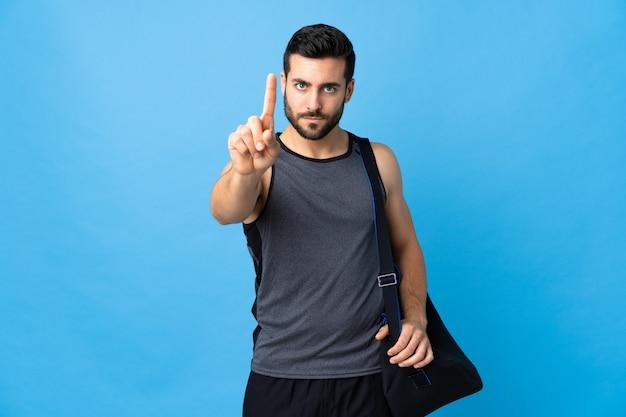 Junger sportmann mit sporttasche lokalisiert auf blauer wand, die einen mit ernstem ausdruck zählt