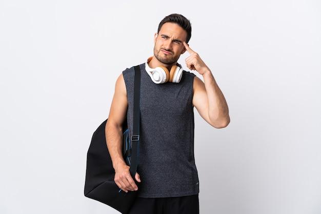 Junger sportmann mit sporttasche lokalisiert auf weiß, das die geste des wahnsinns macht, der finger auf den kopf setzt