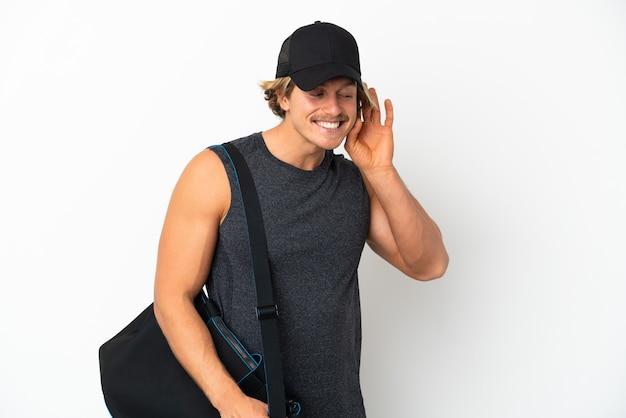 Junger sportmann mit sporttasche lokalisiert auf weißem hintergrund, der etwas hört, indem man hand auf das ohr setzt