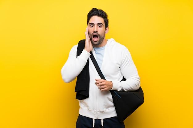 Junger sportmann über lokalisierter gelber wand mit überraschung und entsetztem gesichtsausdruck