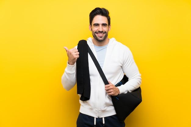 Junger sportmann über lokalisierter gelber wand zeigend auf die seite, um ein produkt darzustellen