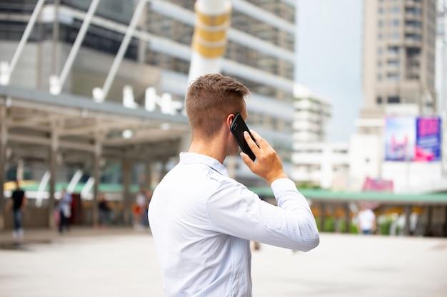 Junger städtischer berufsmann, der intelligentes telefon verwendet. geschäftsmann, der intelligentes mobiltelefon hält