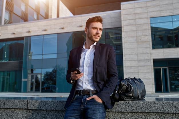 Junger städtischer berufsmann, der intelligentes telefon verwendet. geschäftsmann, der mobilen smartphone unter verwendung der tragenden jacke sms-mitteilung der app simst