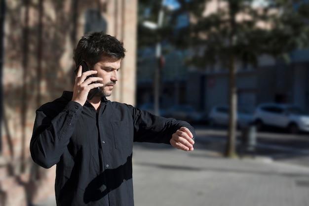 Junger städtischer geschäftsmann auf smartphone in der straße sprechend auf smartphone