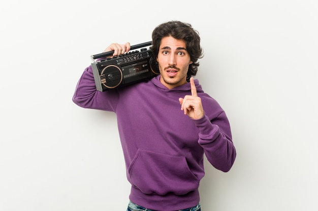 Junger städtischer mann, der einen guetto-blaster hält, der eine idee, inspirationskonzept hat.